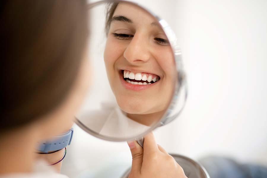 Teenage girl looking at her teeth in the mirror